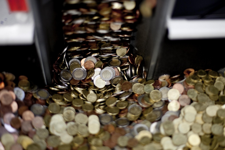 Viele unterschiedliche Münzen in einem Metallschacht